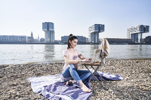 Germany, Cologne, young woman using laptop at River Rhine - FMKF04046