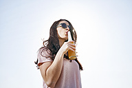 Young woman having a beer under blue sky - FMKF04052