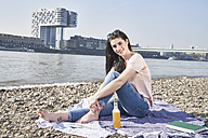 Germany, Cologne, young woman relaxing at River Rhine - FMKF04055