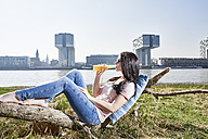 Germany, Cologne, young woman relaxing and having a beer at River Rhine - FMKF04058