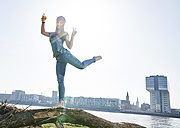 Germany, Cologne, happy young woman with beer bottle at River Rhine - FMKF04061