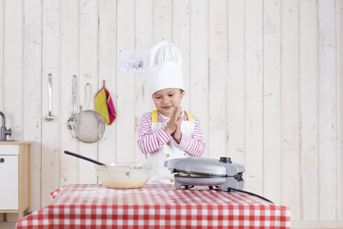 Little girl preparing waffles, wearing chef's hat - DRF01724