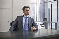 Businessman sitting at desk in office - ZEF13590