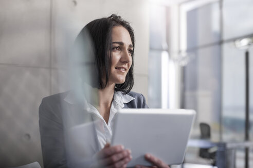 Businesswoman holding digital tablet in office - ZEF13593