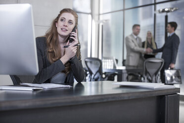 Woman on the phone at office desk - ZEF13596