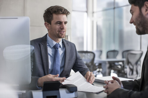Businessman talking to client in office - ZEF13608