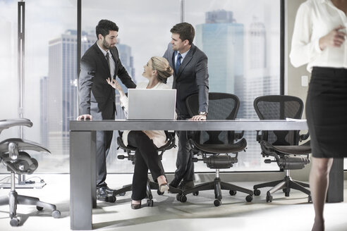 Group of businesspeople with laptop discussing in office - ZEF13644