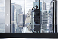 Businessman with rolling suitcase taking photos of city view in office - ZEF13650