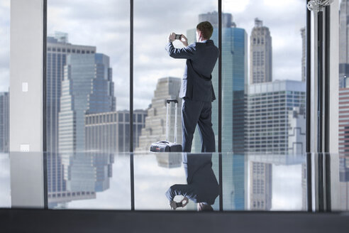 Businessman with rolling suitcase taking photos of city view in office - ZEF13653