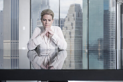 Serious businesswoman sitting at desk in city office looking at cell phone - ZEF13659