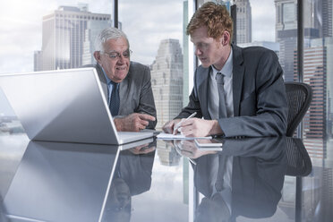 Two businessmen with laptop discussing in office - ZEF13662