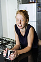 Young woman standing in kitchen, drinking coffee - VABF01344