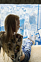 Young woman in high rise building sitting in window, looking over city - VABF01350