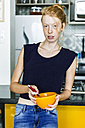Ginger woman standing in kitchen eating breakfast - VABF01356