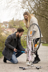 Young man inflating bicycle tire for his girlfriend - MIDF00819
