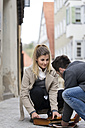 Young man collecting documents of young woman on the street - MIDF00840