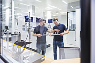 Two men in testing instrument room talking about product - DIGF02150
