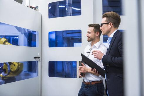 Two men talking in factory shop floor looking at machine - DIGF02165