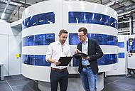 Two men talking in factory shop floor - DIGF02174