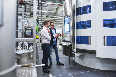 Two men talking in factory shop floor looking at screen - DIGF02177