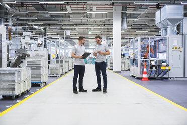 Two men talking in factory shop floor - DIGF02189