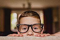Portrait of peeking boy wearing oversized glasses - NMSF00058