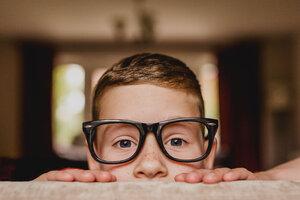 Portrait of peeking boy wearing oversized glasses - NMSF00058