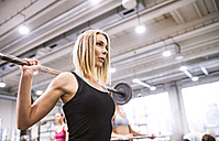 Young woman lifting weights in gym - HAPF01560