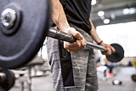 Young man lifting weights in gym - HAPF01563