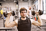 Young man exercising with dumbbells in gym - HAPF01569