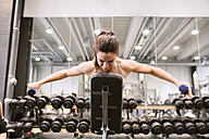 Young woman exercising with dumbbells in gym - HAPF01572
