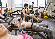 Young woman exercising with dumbbells in gym - HAPF01578