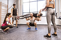 Young people doing fitness training in gym, lifting partners - HAPF01593