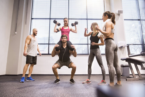 Young people doing fitness training in gym, lifting partners - HAPF01596
