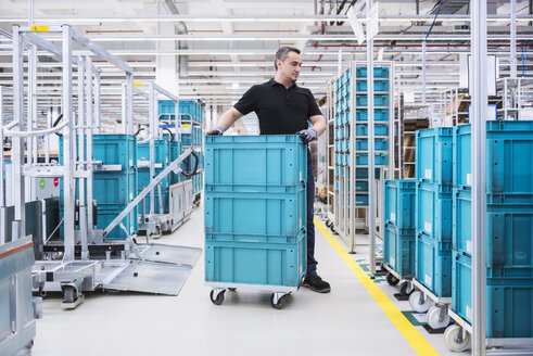Man at tugger train organising boxes in industrial hall - DIGF02209