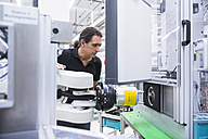 Man operating assembly robot in factory - DIGF02233