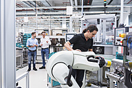 Man operating assembly robot in factory with two men in background supervising - DIGF02242