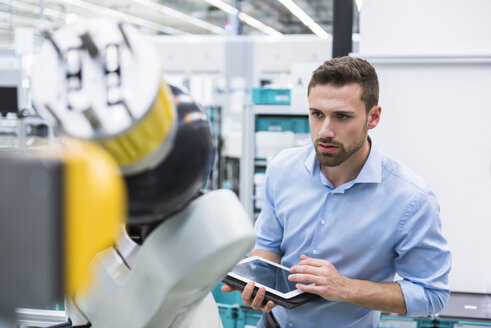 Man with tablet examining assembly robot in factory shop floor - DIGF02251