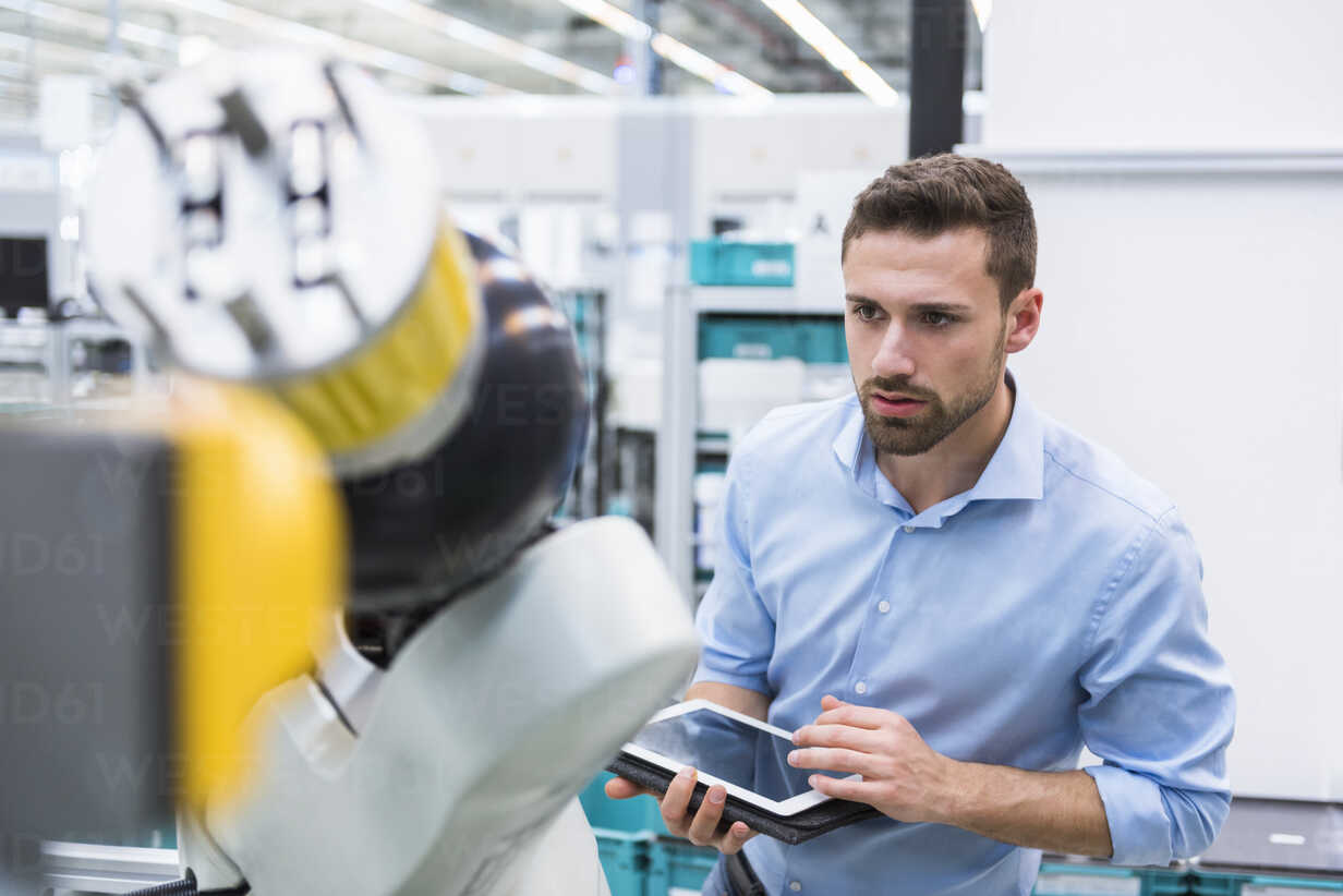 Man with tablet examining assembly robot in factory shop floor - DIGF02251 - Daniel Ingold/Westend61