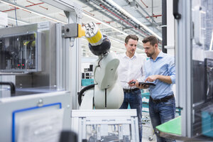 Two men with tablet examining assembly robot in factory shop floor - DIGF02254