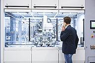 Man in factory shop floor on the phone - DIGF02266