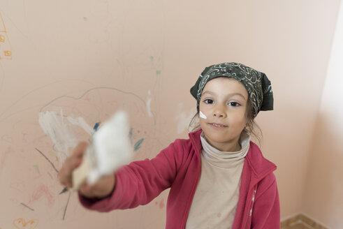 Portrait of little girl painting wall of children's room - JASF01768
