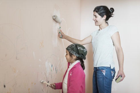 Mother and daughter painting wall in children's room - JASF01774