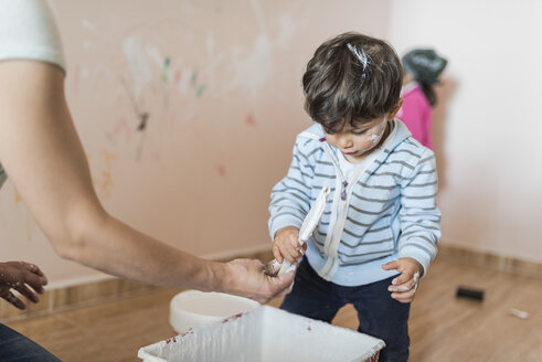 Mother and children painting wall at home - JASF01777