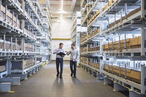 Two men walking in factory warehouse - DIGF02304
