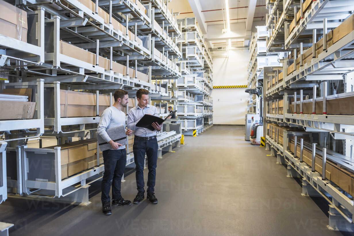 Two men talking in factory warehouse - DIGF02307 - Daniel Ingold/Westend61