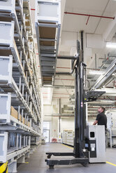 Worker operating forklift in factory warehouse - DIGF02316