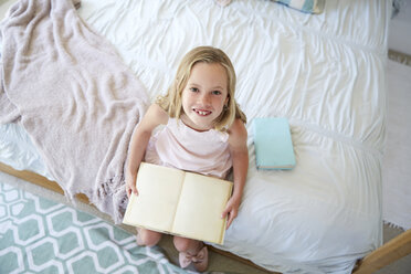 Portrait of little girl sitting on bed with  book - SRYF00253