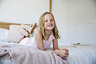 Portrait of smiling little girl with tooth gap lying on bed at home - SRYF00256