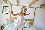 Portrait of smiling little girl dancing on bed at home while listening music with headphones - SRYF00259